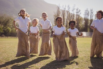 Schoolgirls having fun during sack race in park