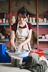 Beautiful woman working at pottery wheel in studio
