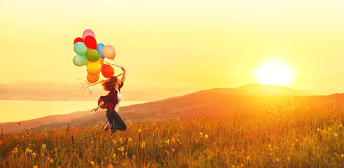 Happy cheerful girl with balloons running across meadow at sunset in summer Wall mural
