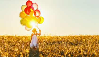 Happy cheerful child girl with balloons on meadow at sunset in summer