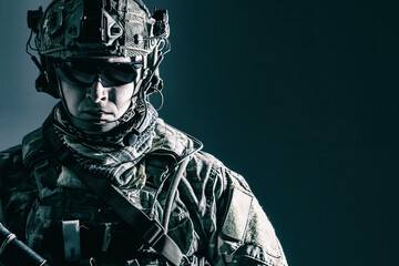 Elite member of US Army rangers in combat helmet and dark glasses. Studio shot, dark black background, looking at camera, dark contrast