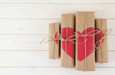 Gift box with hearts. Kraft paper. Background of white wood.