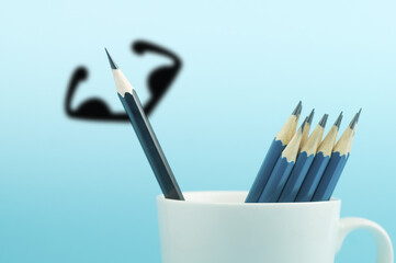 pencil with shadowed muscle in cup on blue background , concept in different and strong