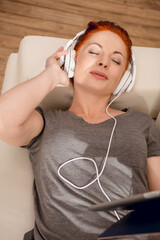 relaxed woman listening music in headphones while lying on sofa