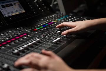 Hands of female audio engineer using sound mixer