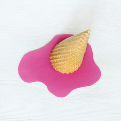 Concept summer heat/ Inverted wafer cone with melted pink ice-cream cut from paper, top view