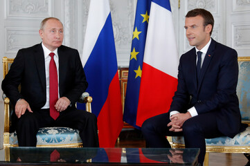 French President Emmanuel Macron meets with Russian President Vladimir Putin at the Chateau de Versailles before the opening of an exhibition marking 300 years of diplomatic ties between the two counties in Versailles