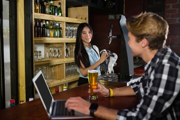 Man having beer while using laptop at counter