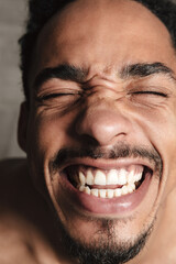 Funny african man isolated over grey background. Eyes closed.