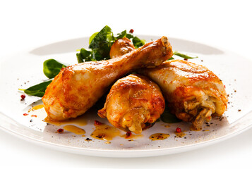 Roast chicken drumsticks on white background