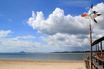 Travel to Island Koh Lanta, Thailand. The bird-weather vane on the background of cloudy sky, blue sea and sandy beach.