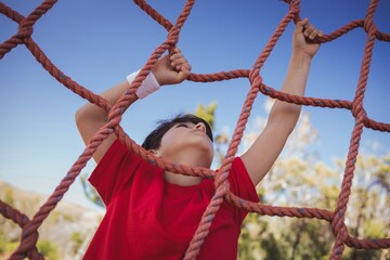 Boy climbing a net during obstacle course training