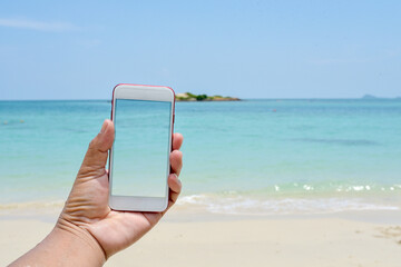 hand hold and touch screen smart phone,cellphone over blurred beautiful beach background abstract background for working on Summer Vacation.