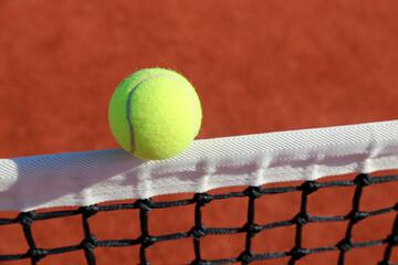 Tennisball berührt das Netz auf rotem Spielfeld, dynamische Perspektive