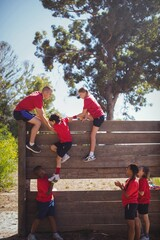 Trainer assisting kids to climb a wooden wall
