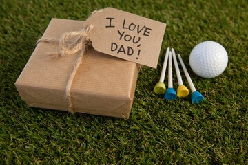 Fathers day gift box and text by golf ball on field