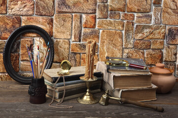 On the table are: old books, a wax candle in a bronze candlestick, a ceramic pot, a pocket watch, tassels in a carved glass and a carved frame for a picture.