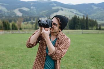 Man makes photos in mountains. Photographer. Traveler. Tourist.