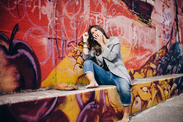 Young pretty woman smoking near a colorful wall with a thoughtful expression. Lifestyle portrait outdoors.