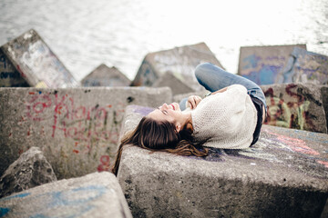 .Young woman sitting on large stone blocks in the seaport of northern Spain. Absolutely carefree lifestyle portrait.