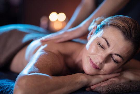 Beautiful senior woman lying on a massage table in a beauty salon
