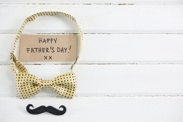Happy fathers day text with bow tie and mustache on table