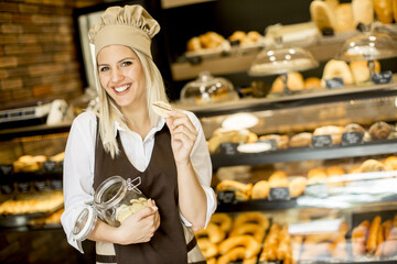 Young woman standing in a bakery with a jar containing biscuits