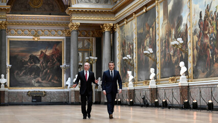 French President Emmanuel Macron and Russian President Vladimir Putin walk in the Galerie des Batailles as they arrive for a joint press conference at the Chateau de Versailles