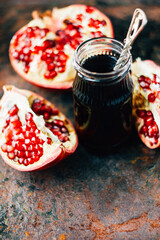 Fresh organic pomegranate sauce in glass jar over rustic surface.