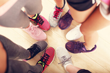 Circle of legs with shoes in a gym