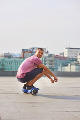 Young man riding hoverboard. Guy on urban background.