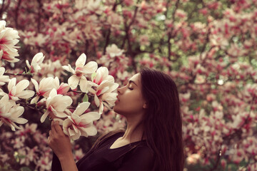 Adorable girl smelling pink, blossoming, magnolia flowers from tree