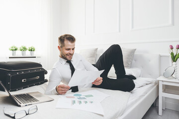Businessman on bed working with a laptop from his hotel room