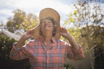 Smiling senior woman wearing sun hat on sunny day