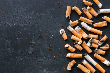 Cigarette butts on a black background with space for text