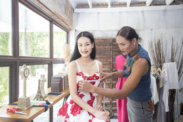 Elegant Asian Woman with beautiful dress sitting for makeup and measure size in vintage showroom, portrait woman with vintage concept,  20s-30s age.