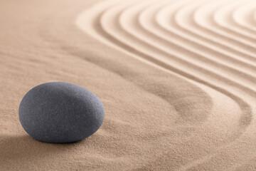 Zen meditation stone garden with rock on raked sand