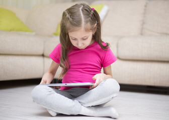Cute child girl playing with a tablet computer.