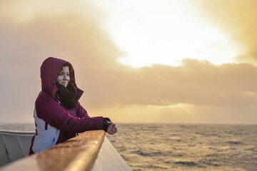 Tourist girl on a boat watching a beautiful sunset over the sea