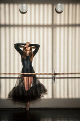 Gorgeous female ballet dancer standing at the wall