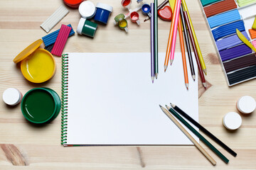 A white sheet of paper, plasticine, pencils and colored paint on the wooden background.