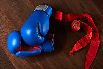 Top view of blue and red boxing gloves and bandage on wooden plank background.