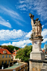 """A view of the Mala Strana district and the sculpture """"The Vision of Saint Luigardi"""" from the Charles Bridge in Prague."""