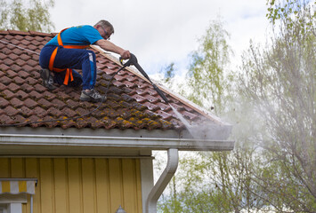 Caucasian man is washing the roof with a high pressure washer. He is wearing safety harness on a slippery roof.