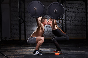 Young beautiful sportive woman and man kissing and lifting a dumbbell from squats against brick wall in the gym.