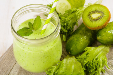 Healthy green smoothie in jar with cucumber, kiwi, salad and spices