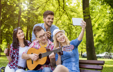 Group of young people having fun in the park while playing guitar and taking selfie
