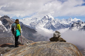 Young Woman hiker with backpack and hiking poles is standing and looking on Ama Dablam mountain. Cloudy sky. Himalaya, Nepal.