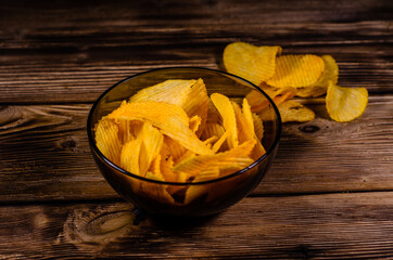 Potato chips in glass bowl on wooden table