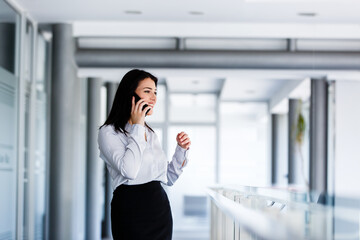 Attractive woman standing while talking on phone in business building